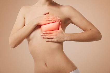 Женщина держится за грудь (рак молочной железы)