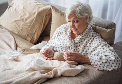 Пожилая женщина принимает таблетки