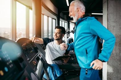 пожилой человек занимается спортом